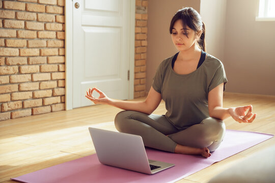 Young healthy indian woman wear sportswear meditating watching live online tv pilates class tutorial on laptop computer at home doing yoga virtual training fitness workout sport exercise in apartment.