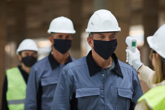 Close up of supervisor measuring temperature of workers with contactless thermometer at construction site, corona virus safety