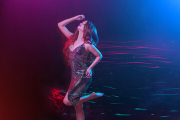 Young beautiful brunette woman in motion. Red blue color mixed light. Attractive girl in shiny evening dress is dancing in night club. Black colorful blue purple background long exposure. Disco effect