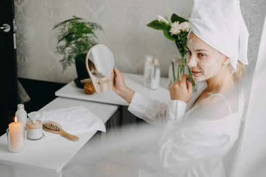 Young woman in white towel chilling in bedroom and making clay facial mask near mirror. Girl doing beauty treatment and relaxing at home. Morning skin care beauty routine, self care