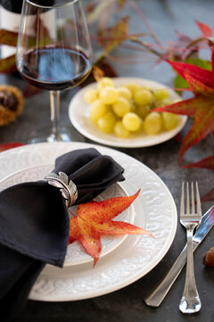 Autumn style dinner table set with red leaves, grapes and a bottle of wine. Selective focus.