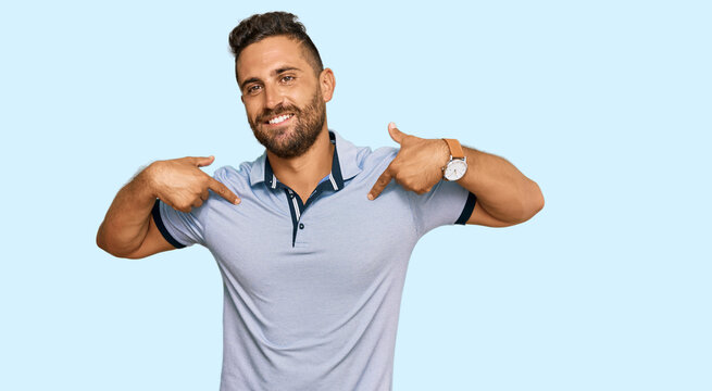 Handsome man with beard wearing casual clothes looking confident with smile on face, pointing oneself with fingers proud and happy.
