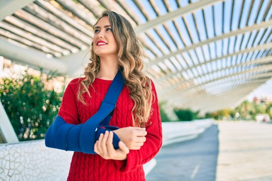 Young blonde girl smiling happy injuried with arm sling standing at the park.