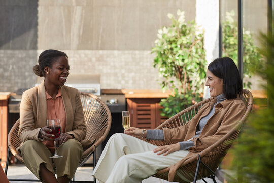 Portrait of two contemporary young women enjoying wine while relaxing in lounge chairs at outdoor terrace, copy space