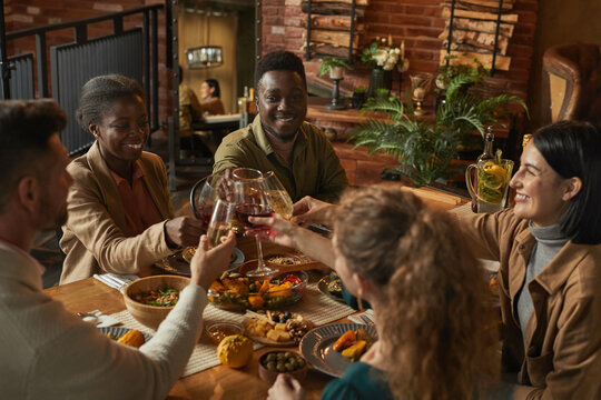 Diverse group of people clinking glasses while enjoying dinner party with friends and family in cozy interior