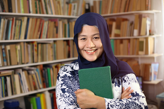 Asian muslim woman wearing hijab reading book in library, educational. Happy smiling expression when doing leisure activity