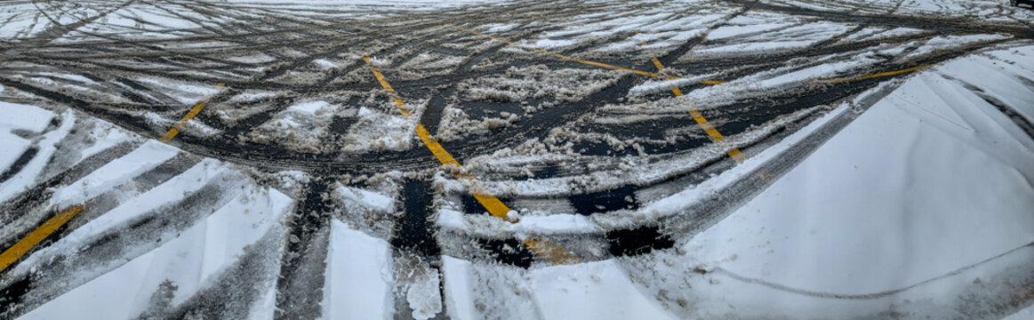 Panoramic view of a parking lot after a snow storm with crisscrossing lines
