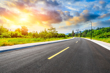 Countryside asphalt road and green plants with mountain natural scenery in Hangzhou at sunrise.