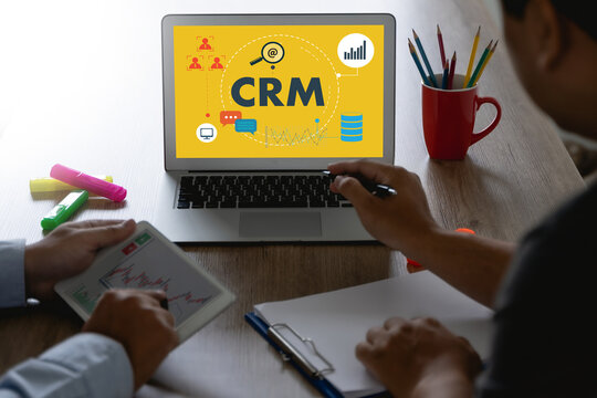 CRM Business Customer CRM Management Analysis Service Concept Business team hands at work with financial reports and a laptop.