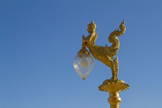 Gold lamps and lighting pole background with a blue sky,at Wat Ban Ngao (Temple), Ranong, Thailand.