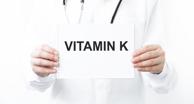 Vitamin K wrote on a card in doctor hands.