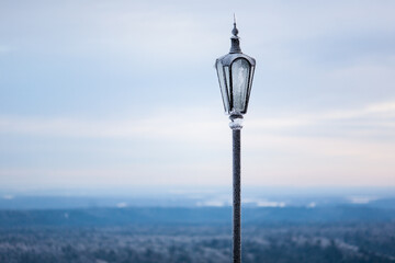 Non-working street lamp on a pole covered with ice, against a background of blue sky and endless forest Fotomurales