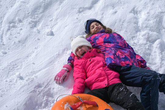 two delightful laughing kids girls wearing ski suit lying on white snow with rubber tube during winter season travel vacation leisure activity with copy space