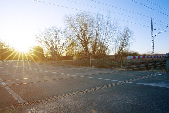 Bahnübergang geschlossene Schranken Sonnenaufgang