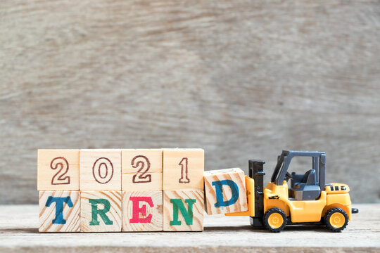 Toy forklift hold letter block D to complete word 2021 trend on wood background