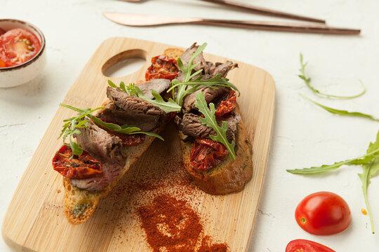 bruschetta made from rye bread in Italian style, smoked meat and sun-dried tomatoes on bruschetta