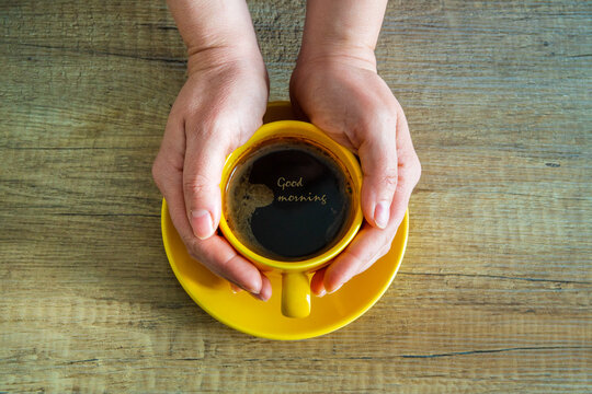 Two hands offering a yellow cup of coffee