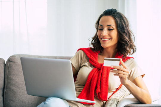 Beautiful happy young woman in casual clothes is sitting on the couch at home and doing online shopping on black friday.