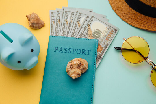Vacation travel adventure trip concept. Minimal simple flat lay with piggy bank, passport and shell on yellow blue background. Tourist essentials.