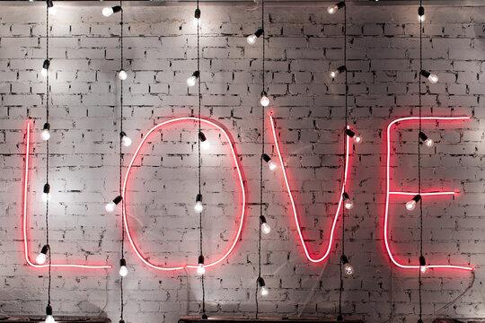 Red neon word Love written on brick wall