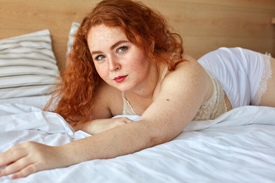 sweet plump woman with curly red hair on the bed at home, pretty large size XXXL loves herself and her body, wearing white lingerie or underwear