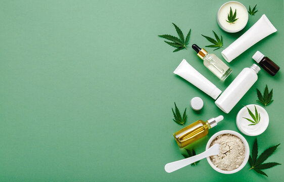 Set of hemp skin care cosmetics in white mockup packaging. Moisturizing cream, Serum, lotion, CBD oil, essential oil cannabis leaves. Flat lay on green background with copy space.