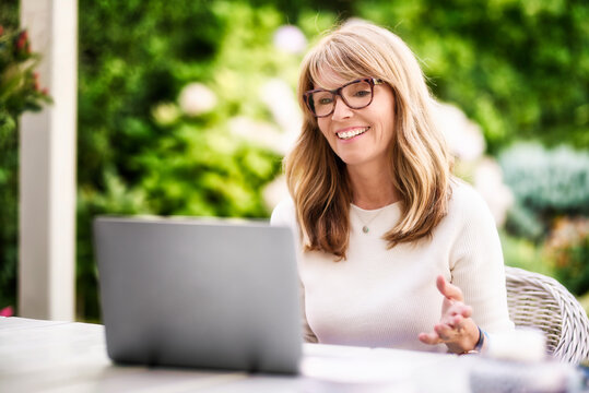 Happy mature woman having video call while sitting in the garden at home
