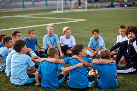 friendly kid boys have rest with trainer during football competition, confident male trainer give advice, explain and have talk with sportive boys, in stadium
