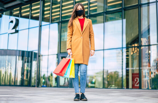 Full length photo of young confident woman in coat and safety medical mask with shopping bags is posing on the mall background