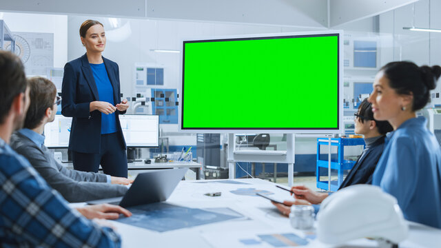 Modern Industrial Factory Meeting: Confident Female Engineer Uses Interactive Green Mock-up Screen Whiteboard, Makes Report to a Group of Engineers, Managers
