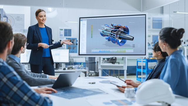 Confident Female Automotive Engineer Reports to Diverse Team of Specialists, Businesspeople and Investors Sitting at the Conference Table, She Use Interactive TV, Analyze Sustainable Energy Engine