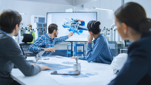 Modern Factory Office Meeting Room: Diverse Team of Engineers, Managers and Investors Talking at Conference Table, Use Interactive TV, Analyze Sustainable Energy Engine Blueprints. High-Tech Facility