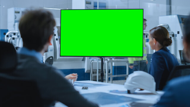 Modern Factory Office Meeting Room: Diverse Team of Engineers, Managers and Investors Talking at Conference Table, Watching Interactive TV that shows Green Screen Chroma Key Mock-up