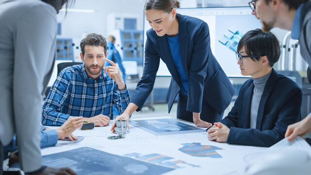Busy Diverse Team of Engineers and Specialists Gather Around Conference Table, They Discuss Project Drafts and Blueprints, Find Problem Solutions. Industrial Technology Factory / Office Meeting Room