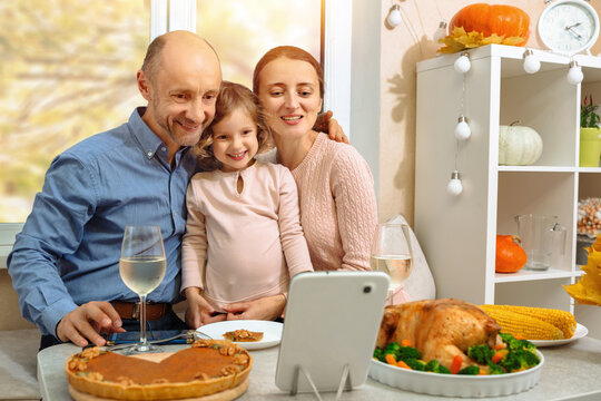 A happy family have a thanksgiving dinner and sends a video greeting to their parents.