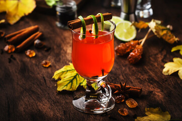 Hot rum punch, grog, autumn or winter warming alcoholic cocktail with dark rum, port, honey, lime juice, black tea, cinnamon and cloves in tall glass on vintage wooden background
