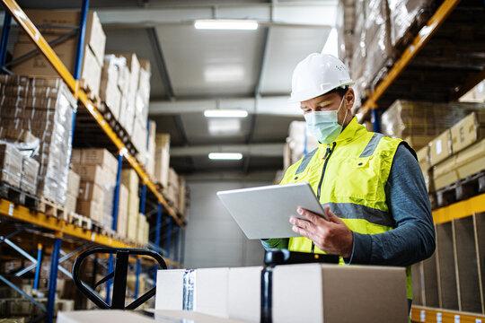 Man worker with tablet working indoors in warehouse, coronavirus concept.
