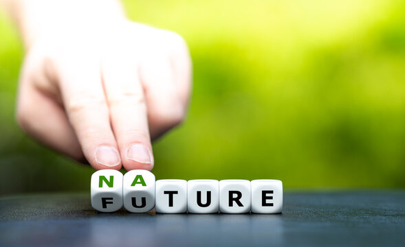 """Hand turns dice and changes the word """"future"""" to """"nature""""."""
