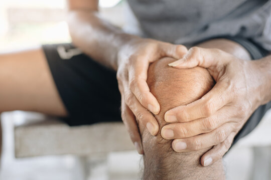 Young man rubs a massage cream on his knees, Knee pain, Pain relief