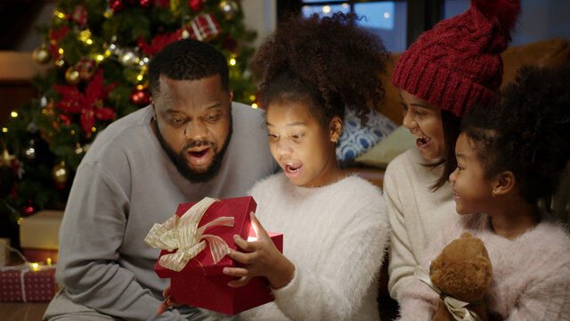 Christmas day, Happy black family at home. African american father, mother and child opening shine light xmas gift box. Cute daughter feeling excited and happy with present.