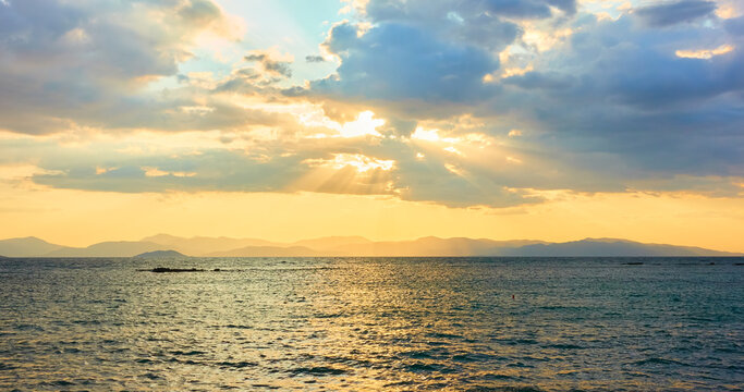 Panoramic view with the sea, clouds and sunbeams