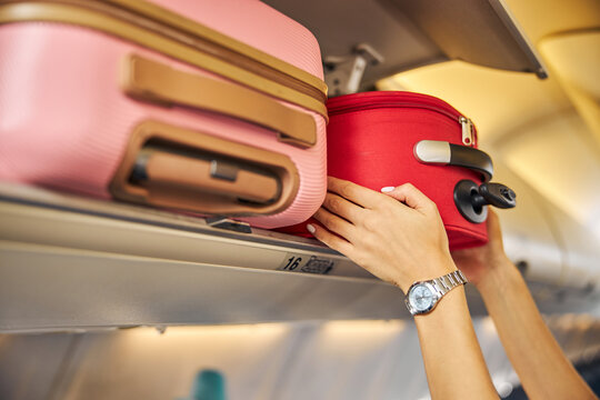 Hands laying down a carry-on baggage on an upper shelf