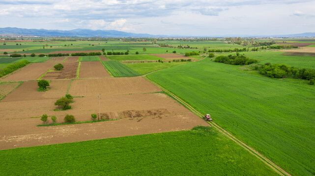 Aerial view tractor spraying the chemicals on the large green field.