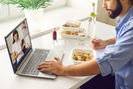 Young man having virtual lunch with wife or girlfriend during break at work or in home office