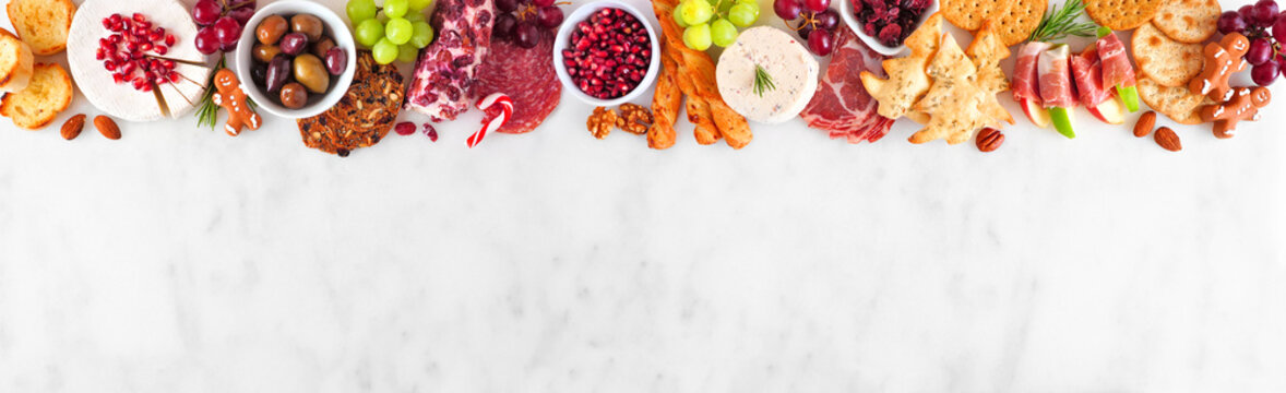 Christmas charcuterie top border against a white marble banner background. Variety of cheese and meat appetizers. Copy space.
