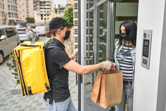 A courier with a backpack and food delivered an online order to the customer's home. The woman received her delivery near the door of her house