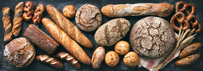 Delicious freshly baked bread assortment on dark rustic background