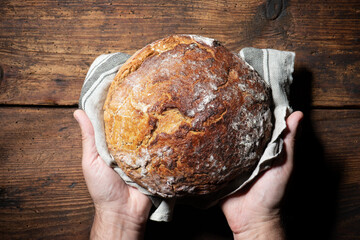 Baker's hands holding and presenting fresh baked loaf of bread