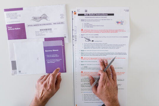 careful hands reading and completing absentee ballot vote by mail