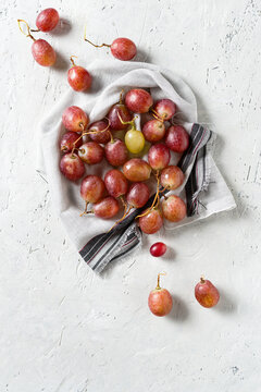 Top view of pink grapes on delicate grey stone background. Copy space.